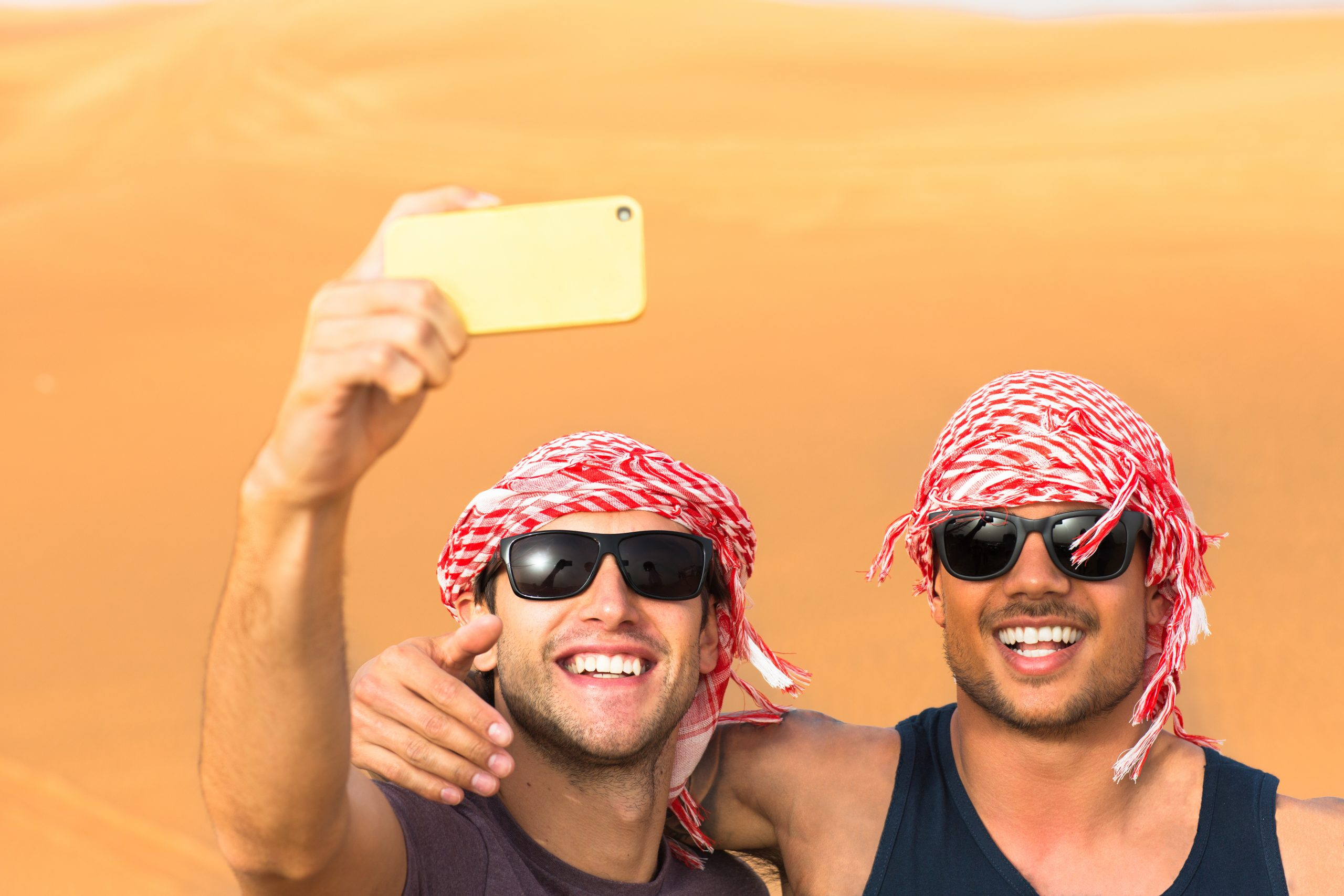 Tourism and Friendship - Happy young male adult friends taking a selfie together during their travels in Arabian desert dunes safari.