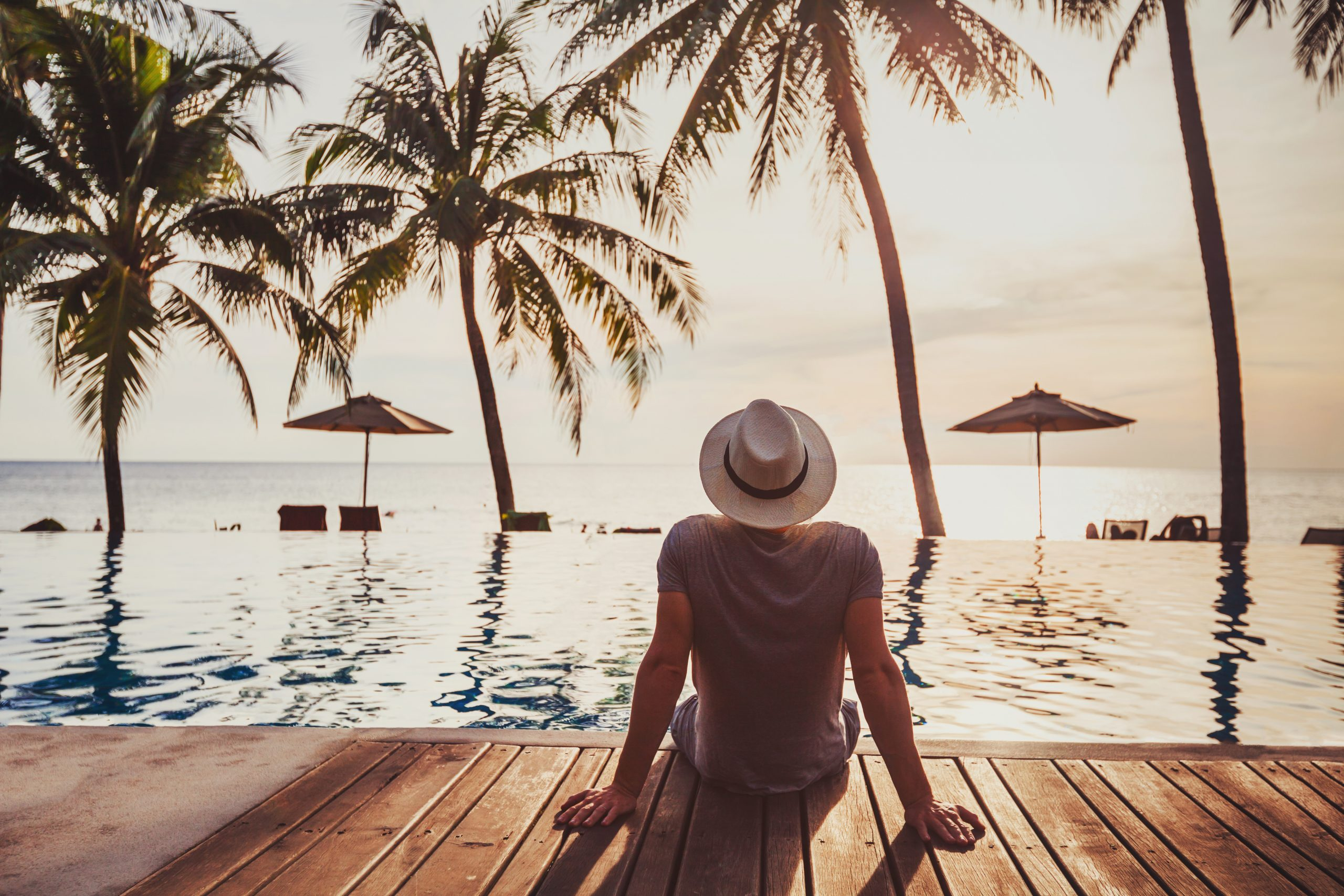 tourist in luxury beach hotel near luxurious swimming pool at sunset, tropical exotic holidays vacation, tourism and travel